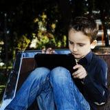 Kind mit Tablette draußen in einem Park Stockfotografie