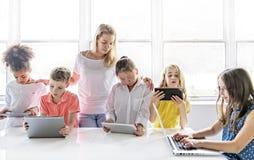 Kind mit Technologietablette und Laptop-Computer im Klassenzimmerlehrer auf dem Hintergrund lizenzfreie stockfotografie