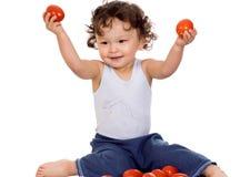 Kind mit Tomate. Stockfotografie
