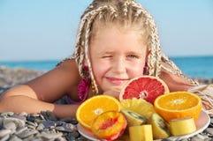 Kind mit tropischer Frucht lizenzfreie stockbilder