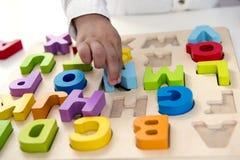 Kind mit zwei Jährigen, das mit Buchstaben spielt Lizenzfreies Stockfoto