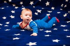 Kind 6 Monate alte und auf einer blauen Decke des sternenklaren Himmels zu Hause lächeln Stockbilder