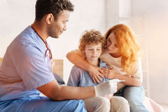 Kind mother embracing her son while visiting doctor Stock Images