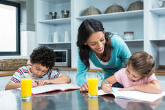 Kind mother helping her children doing homework Stock Photos