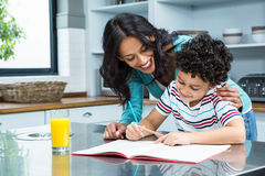 Kind mother helping her son doing homework Stock Photos