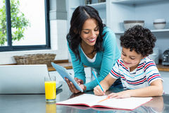 Kind mother helping her son doing homework in kitchen Stock Images