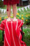 Kind in nationaal kostuum die zich op een kruk bevinden Royalty-vrije Stock Foto's