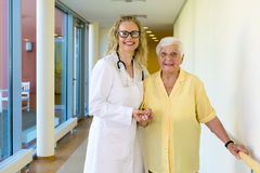 Kind Nurse Assisting Old Patient at the Hallway Stock Images
