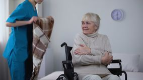 Kind nurse covering with blanket handicapped old woman shivering from cold stock video footage