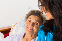 Kind Nurse with Elderly. Kind nurse easing elderly lady's days in nursing home with care help and joy stock photo