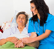 Kind Nurse with Elderly. Kind nurse easing elderly lady's days in nursing home with care help and joy Royalty Free Stock Photos