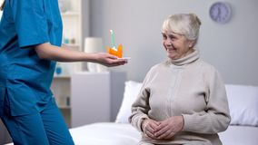Kind nurse giving birthday cake to aged lonely woman, taking care in old age. Stock photo stock photo