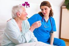 Kind nurse listening to senior sick woman royalty free stock images
