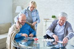 Kind nurse taking care of senior people. Woman caring for elderly patients covering men with plaid while playing lotto with friend in assisted living home Stock Photography