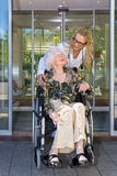 Kind Nurse Talking to Elderly Woman on Wheelchair royalty free stock images