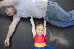 Kind oben gekleidet wie ein Superheld, der ihren Vati anhebt Lizenzfreies Stockbild