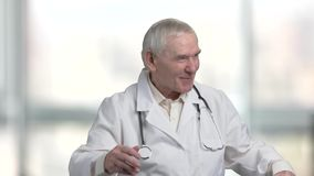 Kind old doctor cheering you up. Speech of old cheerful pediatrician, bright blurred windows in hospital background stock video footage