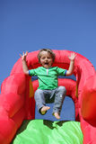 Kind op de opblaasbare dia van het bouncykasteel Stock Foto's