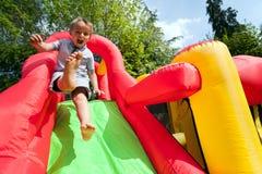 Kind op de opblaasbare dia van het bouncykasteel
