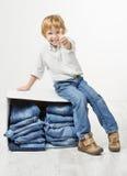 Kind op doos met jeans. Het tonen beduimelt omhoog stock foto's
