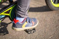 Kind op een fiets bij asfaltweg Fiets in zich park het bewegen stock foto's
