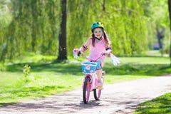 Kind op fiets De fiets van de jonge geitjesrit Meisje het cirkelen royalty-vrije stock afbeeldingen