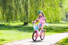 Kind op fiets De fiets van de jonge geitjesrit Meisje het cirkelen royalty-vrije stock foto's