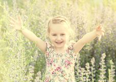 Kind op gebied onder bloemen en kruiden, het glimlachen royalty-vrije stock foto