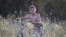 Kind op rust in een dorp met een fiets in een hoog gras stock video