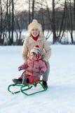 Kind op slee met moeder in de winter Stock Afbeelding