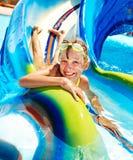 Kind op waterdia bij aquapark. Stock Afbeeldingen