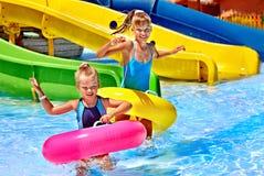 Kind op waterdia bij aquapark Stock Foto
