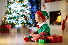 Kind openen huidig bij Kerstboom thuis Jong geitje in elfkostuum met Kerstmisgiften en speelgoed  stock foto's
