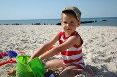 Kind playint mit Spielwaren auf dem Strand Lizenzfreie Stockfotos
