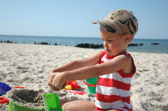 Kind playint mit Spielwaren auf dem Strand Stockbild