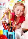 Kind prescooler mit Bleistift im Spielraum. Stockfotografie
