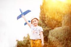 Kind proefvliegenier met vliegtuigdromen van het reizen in de zomer in aard bij zonsondergang stock afbeelding