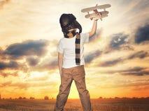 Kind proefvliegenier met vliegtuigdromen van het reizen in de zomer in aard bij zonsondergang royalty-vrije stock fotografie