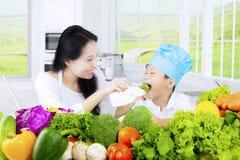 Kind proevende salade met zijn moeder stock afbeelding