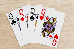 4 of a kind queens - casino playing poker cards. 4 of a kind queens - winning hand of gambling casino poker playing cards on a table royalty free stock photos