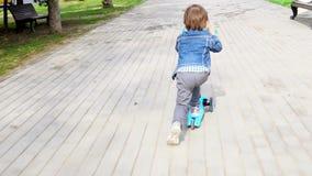 Kind reitet einen Roller in einem Park Sorglose Kindheit stock video footage