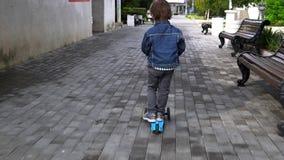 Kind reitet einen Roller in einem Park Sorglose Kindheit stock video
