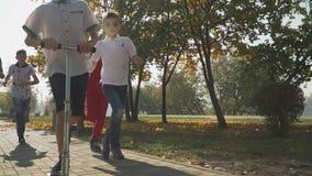 Kind reitet einen Roller im Herbstpark Freunde holen einen Jungen ein, der draußen einen Roller reitet Kinder, die herein spielen stock video footage