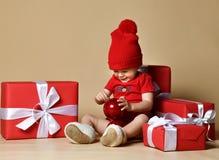 Kind in rode hoed met stapels huidige dozen rond het zitten op de vloer royalty-vrije stock afbeelding