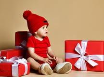 Kind in rode hoed met stapels huidige dozen rond het zitten op de vloer stock fotografie