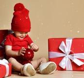 Kind in rode hoed met stapels huidige dozen rond het zitten op de vloer royalty-vrije stock afbeeldingen