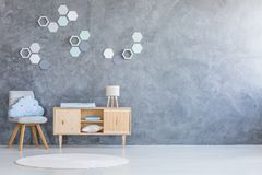 Kind room with hexagon decoration. Kind room interior with hexagon decoration on empty gray wall and blue cloud cushion on simple wooden chair royalty free stock images