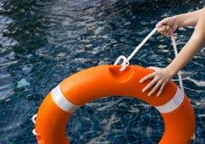 Kind `` s übergibt das Halten des Rettungsrings gegen gefährliches dunkles Wasser im Swimmingpool Sicherheit, Elternfurchtkonzept stockbilder