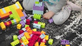 Kind-` s übergibt das Spielen mit Erbauerziegelsteinen stock footage