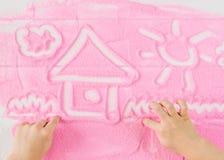 Kind-` s übergibt Farbe ein schönes Bild auf dekorativem Sand Stockfoto